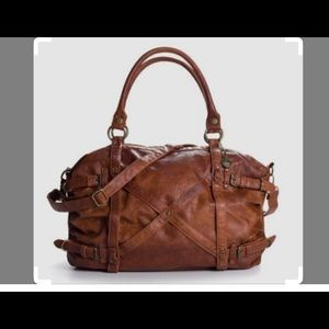 Travel bag with gold hardware, top zip closer.